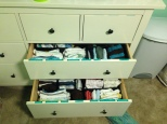 The drawers are filled with tiny, washed clothes that have been meticulously labeled.
